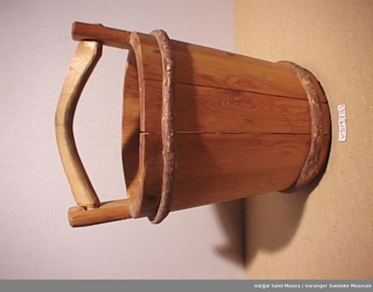 Moderne reproduksjon av trebøtte av gammel type. Satt sammen av staver som er festet sammen med bånd. Håndtak og hank av tre.