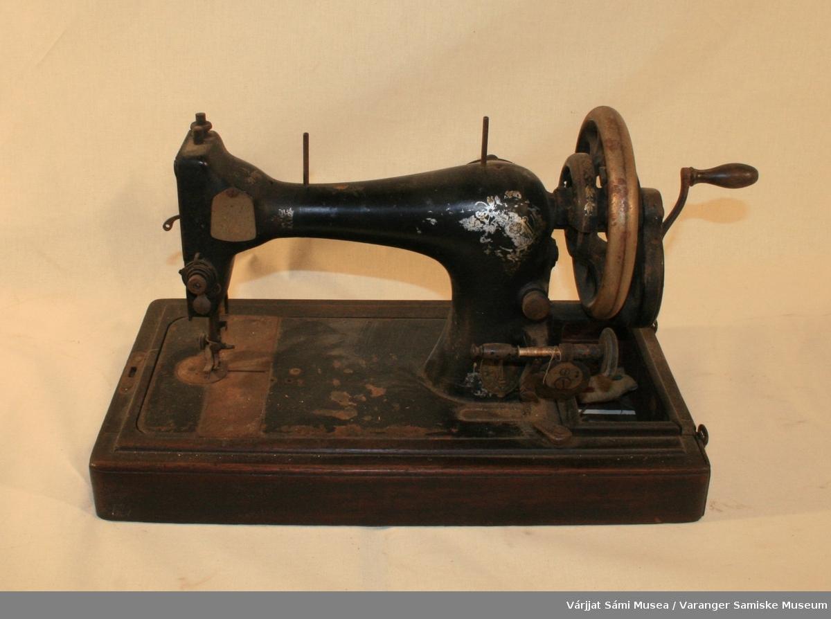 Hånddrevet symaskin fra Singer, selve maskinen er av sortmalt metall mens foten / sokkelen er av brunt tre.