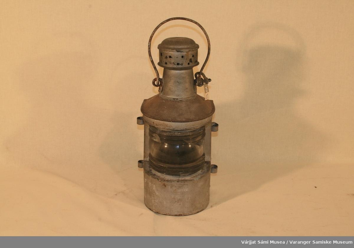 Lanterne av grått metall, sannsynligvis sink.  Inni lanterna ligger en parafinlampebrenner.