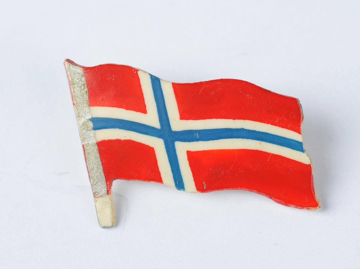 Jakkemerke i plast utforma som eit norsk flagg.