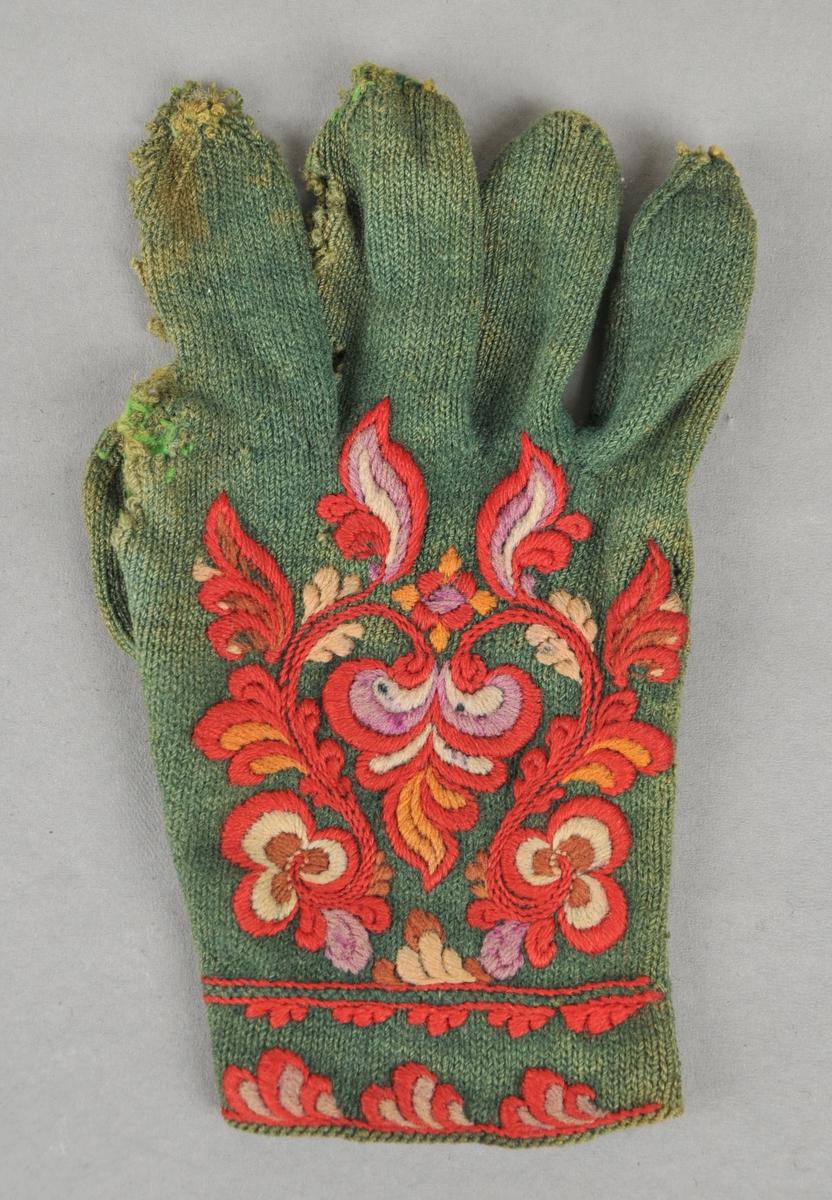 Strikka fingervott i tynnt grønt 2 tråds spelsau-ullgarn. 4 masker pr cm. Stoppa med lysare grønt ullgarn. Rosesauma med ullgarn på øvre kanten, på handbaken og på tommelen.