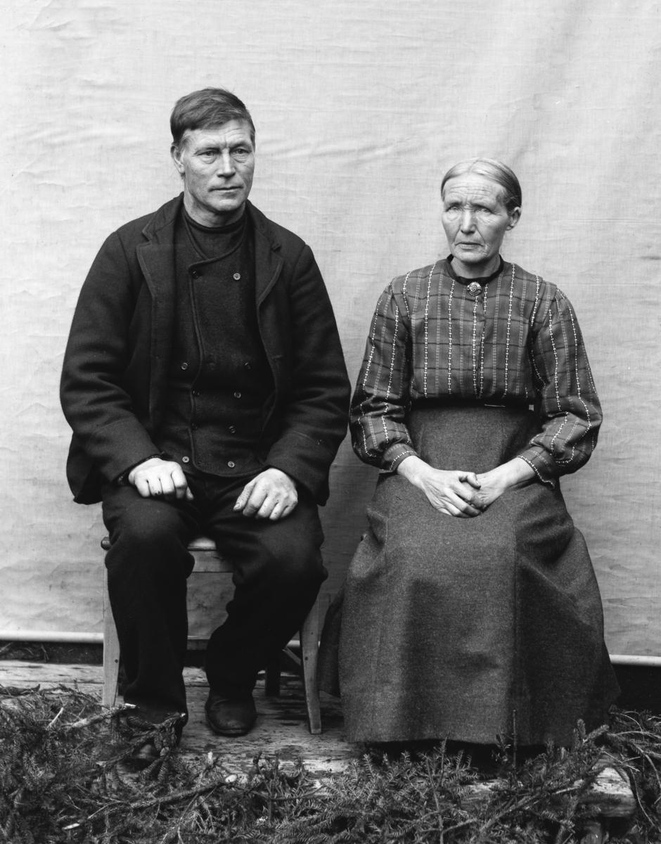 Kvinne og mann sittende foran hvitt lerret