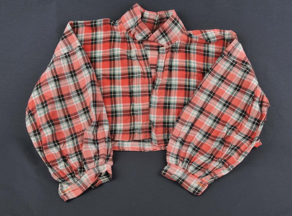 Rutete kvardagsskjorte/bluse med lange armar og påmontera mansjettar med knappar. Spiss krage, påsette stolpar framme uten knapping.