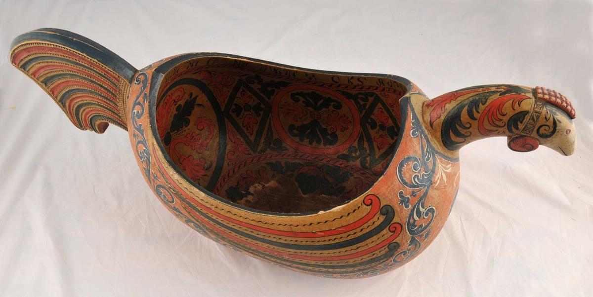 Uthola av eit stykke tre, forma som ein fugl med hovud og stjert, er dekorera med karveskurd..Rosemåling inne i kana og utvendig. Drikkevers langs kanten inni.