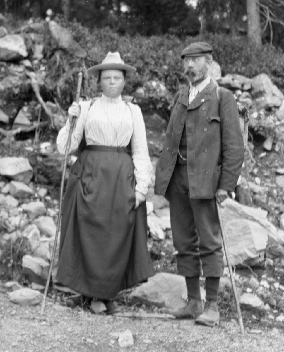 Kvinne og mann med hver sin stav, steinrøys og skog i bakgrunnen