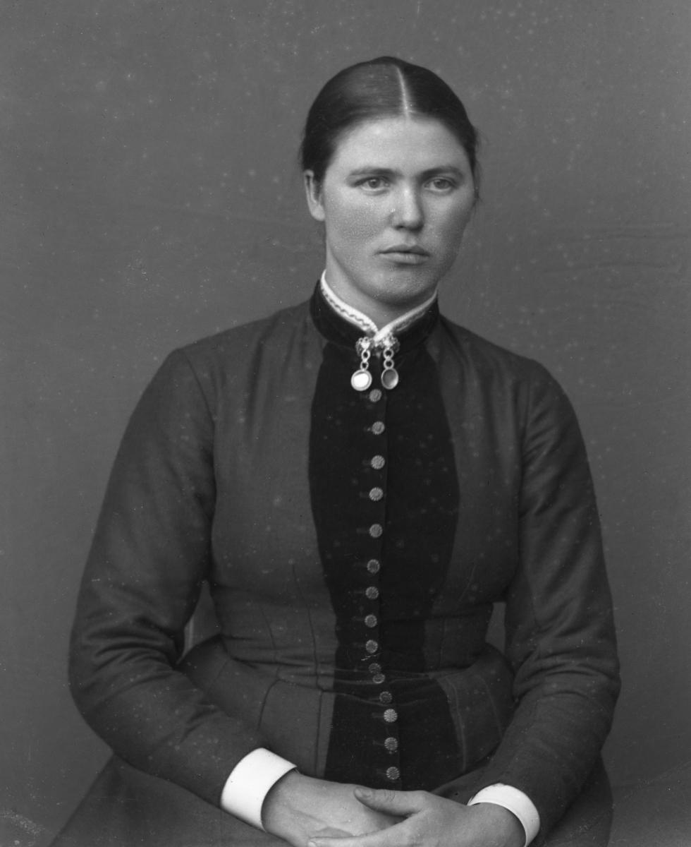 Mørkkledd kvinne i halvfigur, lerretbakgrunn