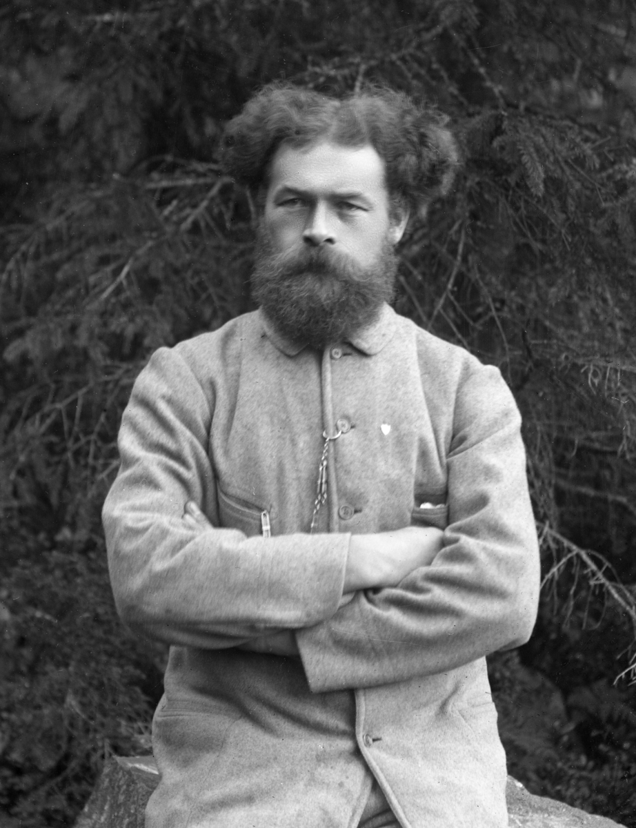 Mann kledd i lys dress, sittende på trestubbe med skog i bakgrunnen