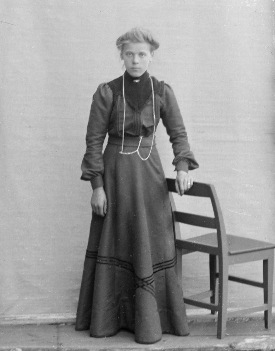 Ung kvinne kledd i mørk kjole, avbildet stående ved stol, foran lerret på husvegg