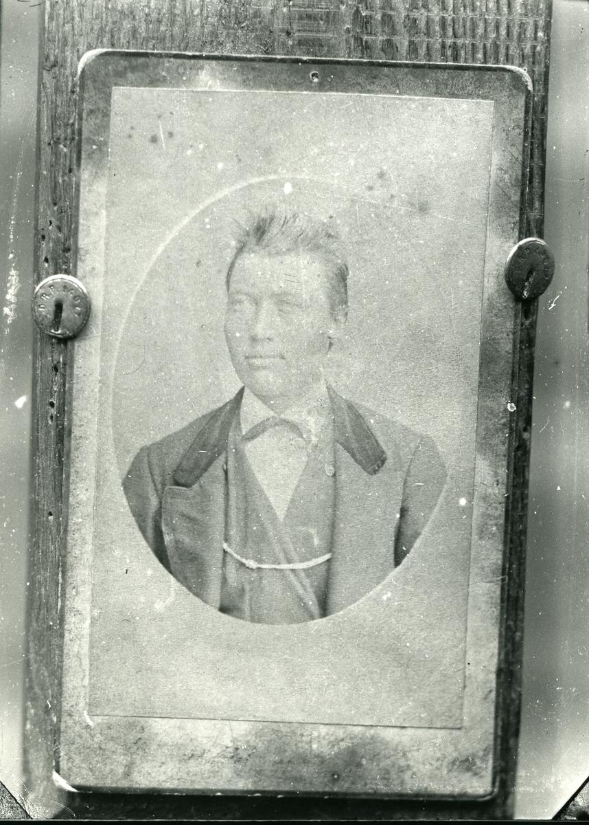 Fotografi av fotografi festet på treplate med tegnestifter. Brystbilde av mann