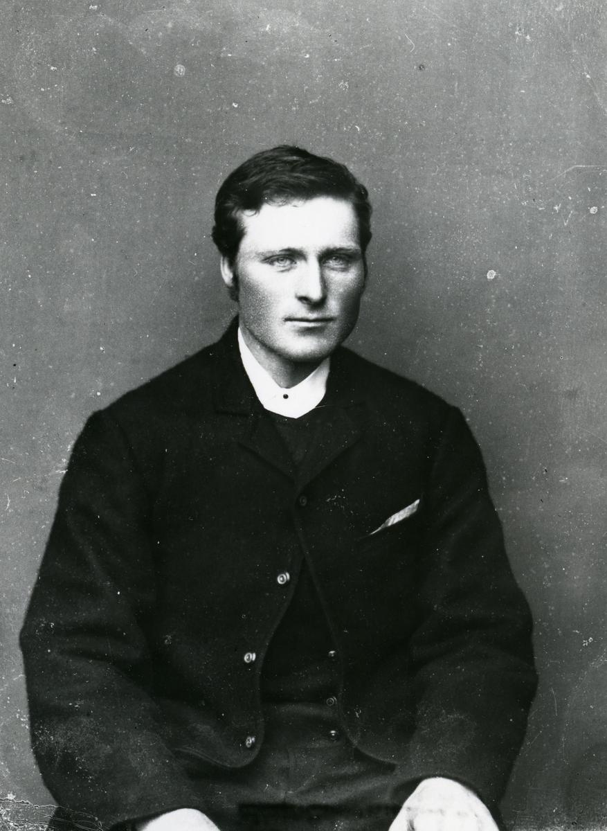 Mann sittende foran lerret, halvfigur