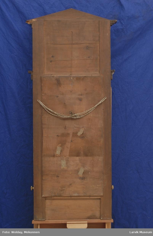 Form: rekt.speil i ramme med høyt toppstykke med uttrappet røstformet topp. over speil, rundbue med forgylt list i stukk, båret av to glatte søyler.