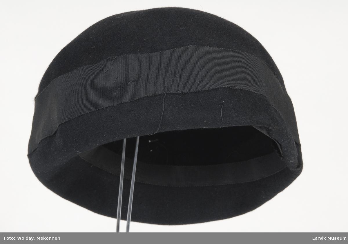 Form: sort filt, sort ripsbånd langs kanten og på