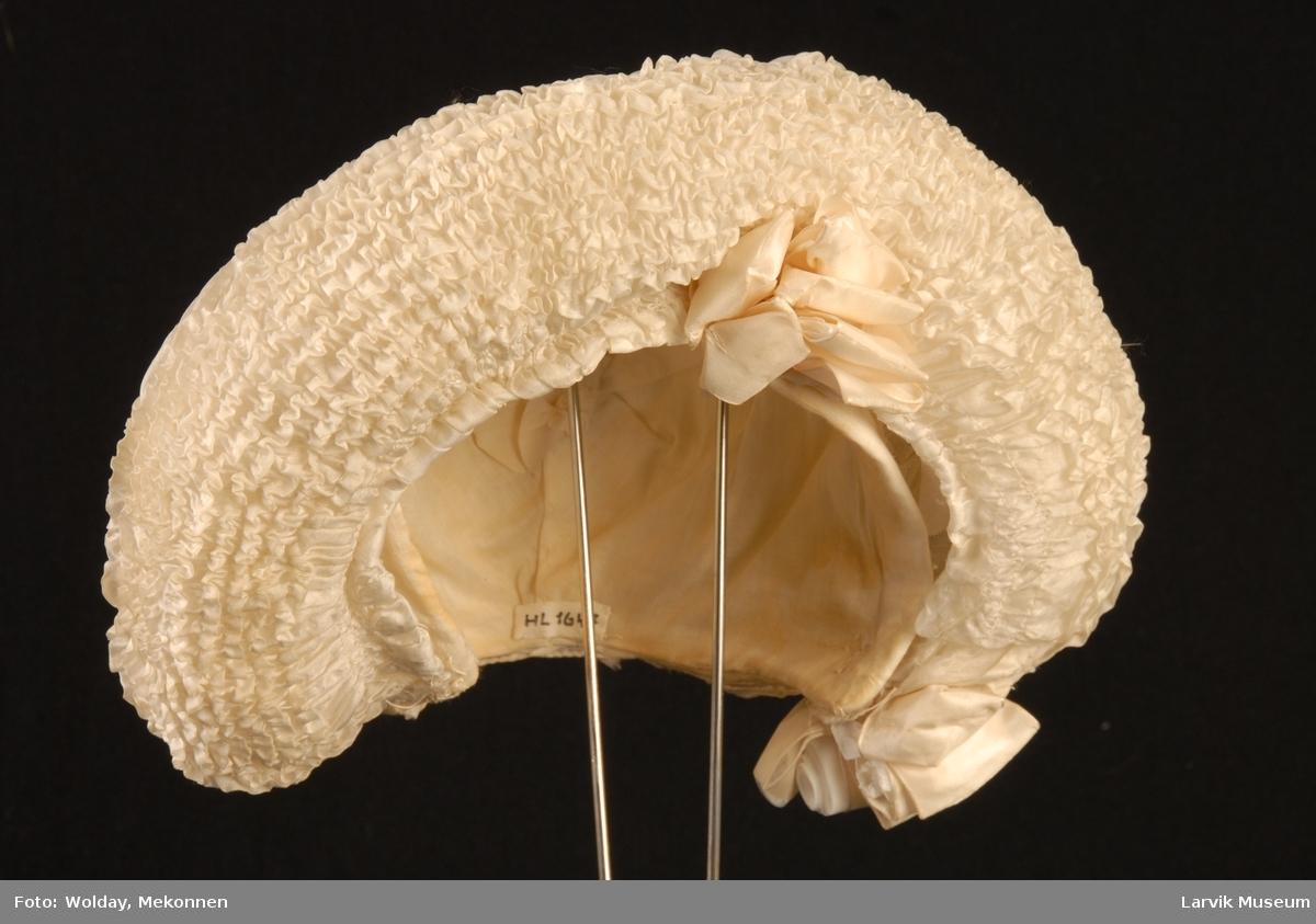 Form: pull som følger bakhodets form,en bord med  hullsøm fra nakken fremover,flankert av tette rader rysjer,små silkerosetter i nakken,rund,luftig brem,av tett rynket silke,en silkerosett på venstre panneside,én der bremmen slutter bak