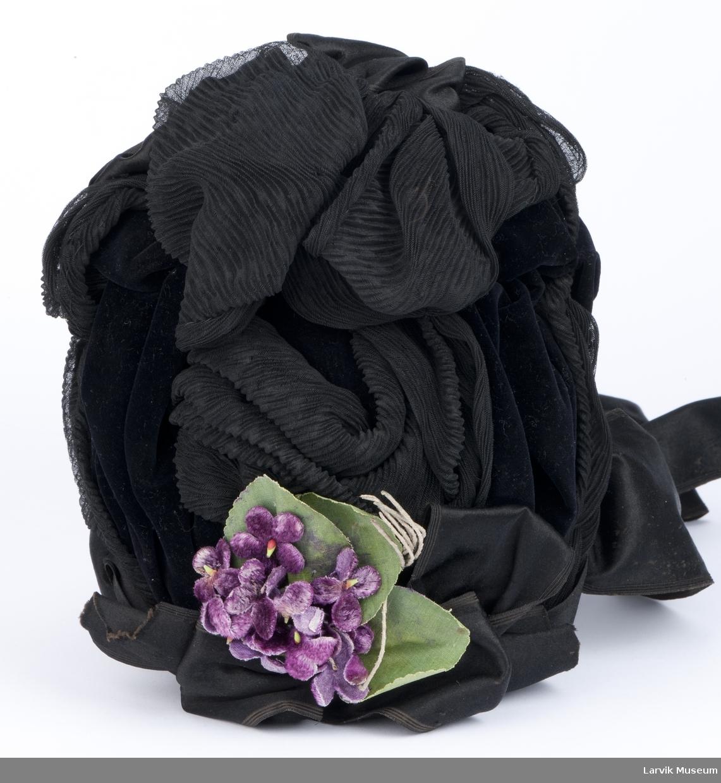 Form: sort fløyel, dandert med plissert sort chiffon og sort silkesatengsløyfe foran og bak,Violbukett m.b.,sorte satengbånd til knyting under haken,sort,glittet fór med etikett
