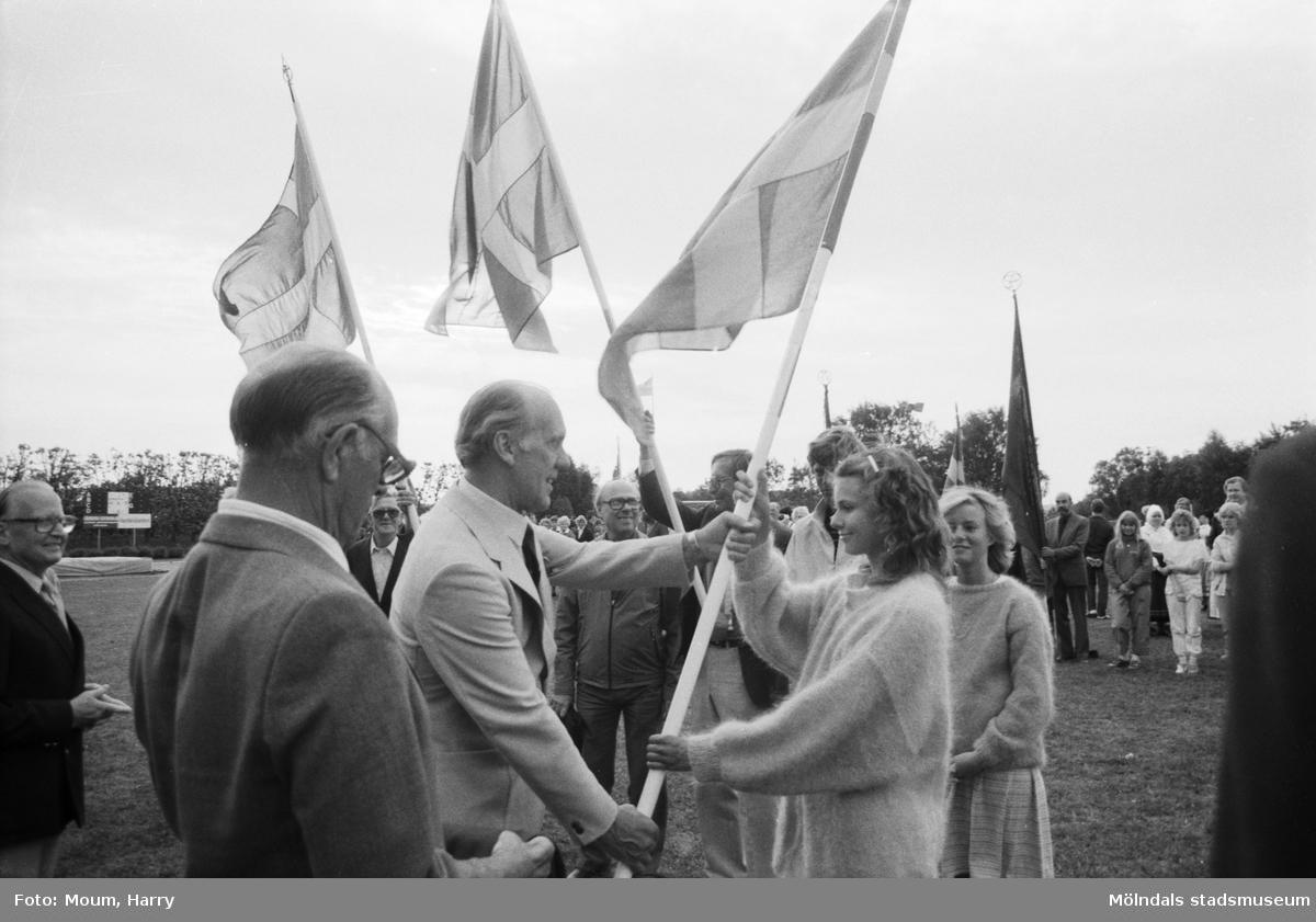 """Nationaldagsfirande på Kvarnbyvallen i Mölndal, år 1984. """"Kommunfullmäktiges ordf. Sven Olsson överlämnar en fana till Ekenskolan."""" På bilden ses även Lage Lindberg och Erik Gustavsson.  För mer information om bilden se under tilläggsinformation."""