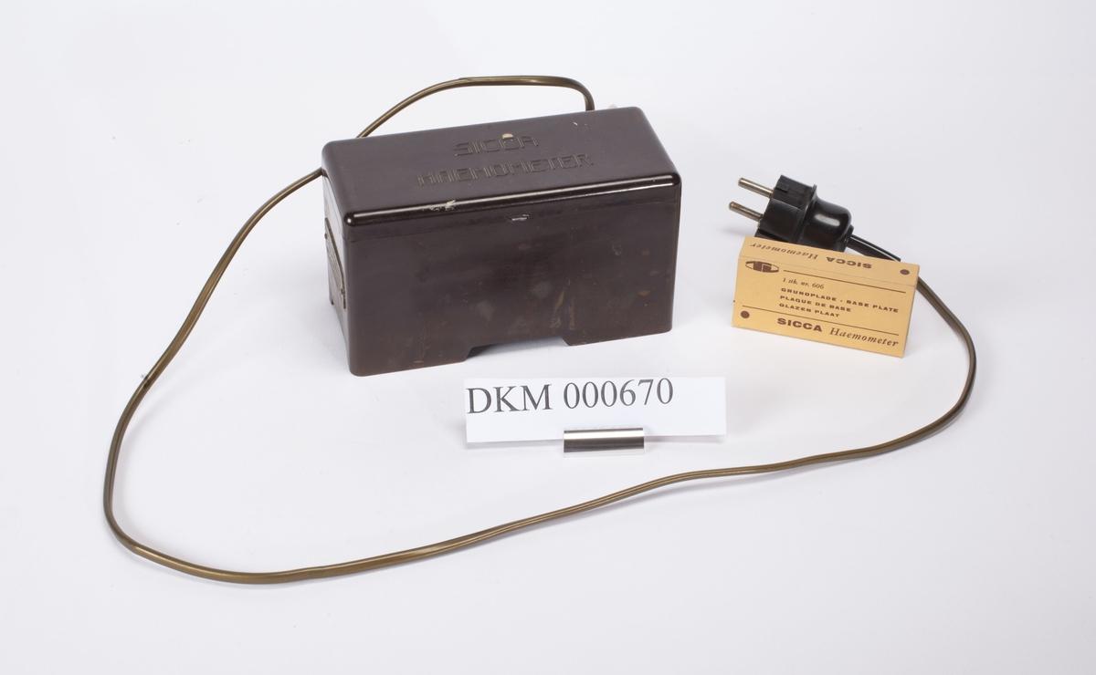 Apparatet er innebygd i en rektangulær kasse med lokk. Det har strømledning, og en løs grunnplate i glass.