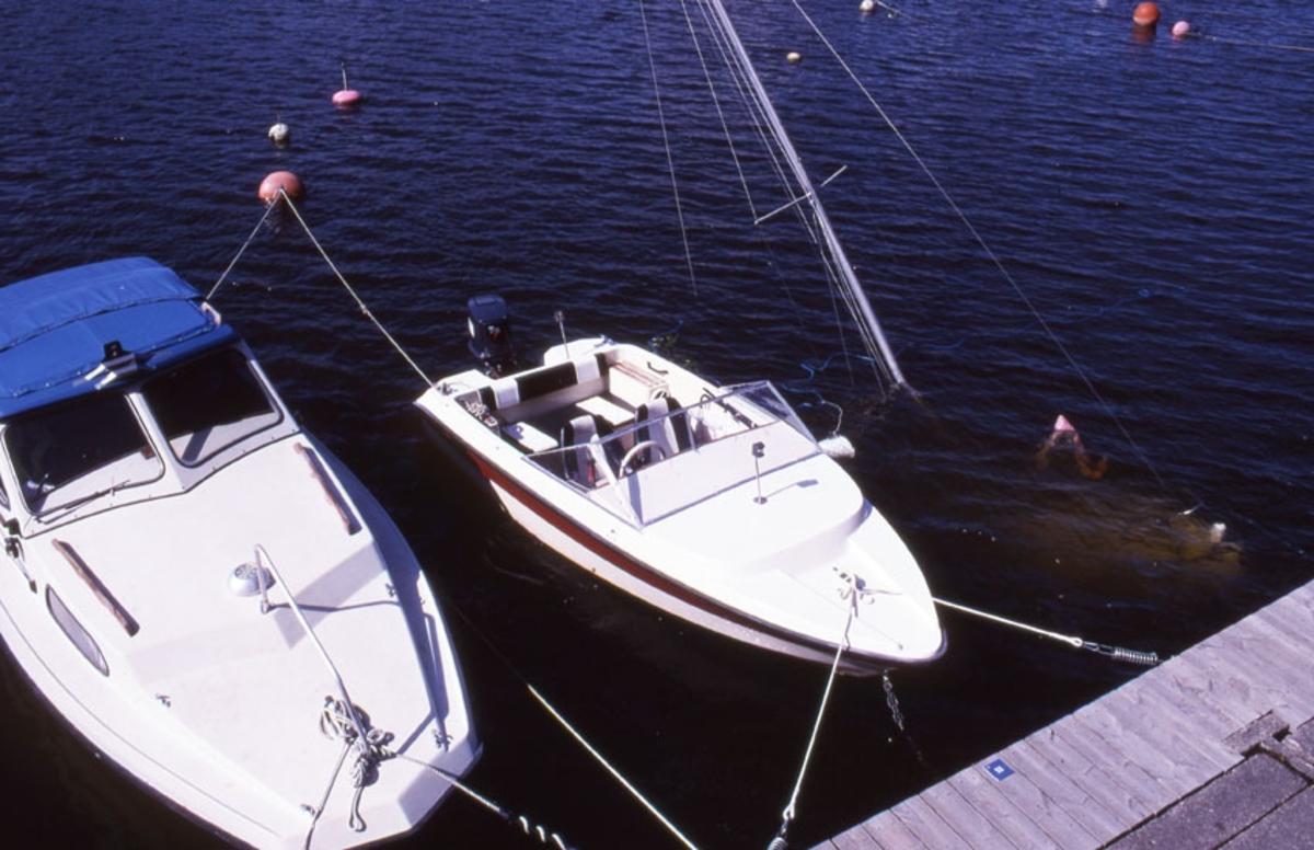 Södermalm. Kabinbåt, möjligen Fisksätra, daycruiser liknande Flipper samt sjunken segelbåt.