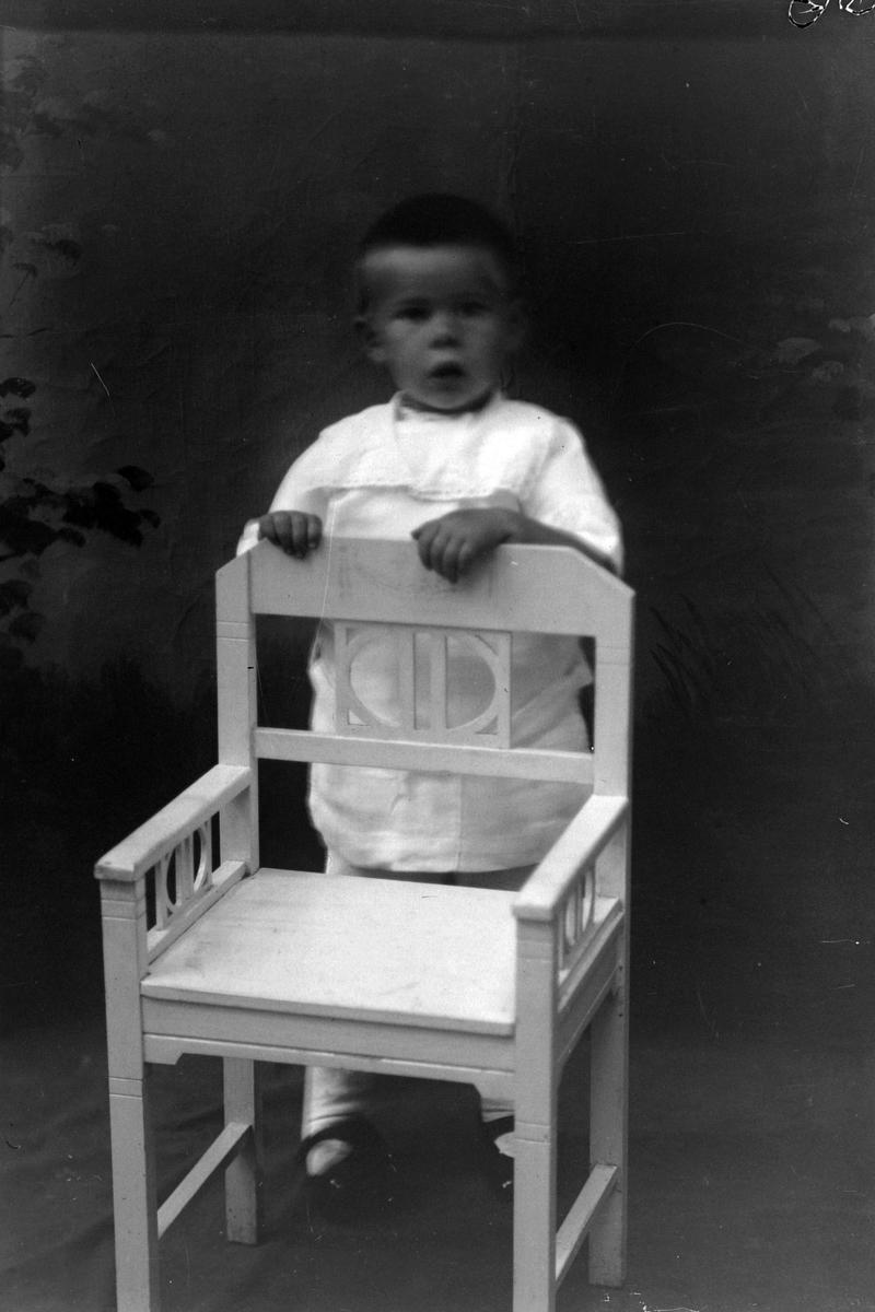 Studioportrett av et lite barn som står bak en stol.