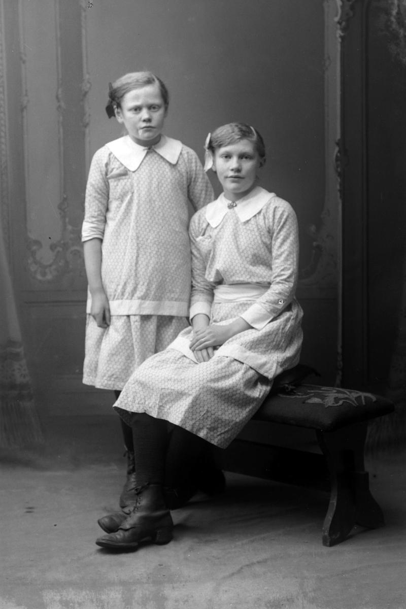 Studioportrett av to unge jenter med sløyfer i håret.