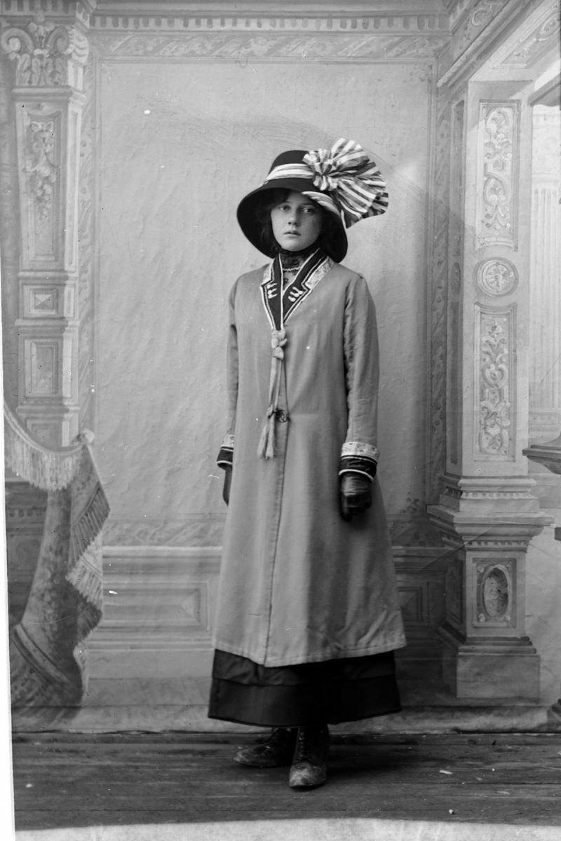 Studioportrett av en kvinne med stor hatt på hodet.