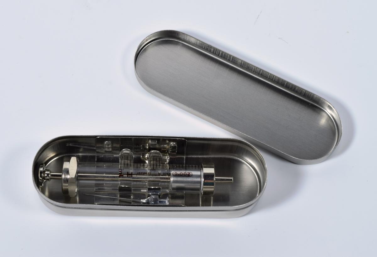 """Oval metalleske som inneholder en sprøyte og to sprøytespisser. Esken, både bunn og lokk, er sølvfarget og helt uten merker eller stemplet av noe slag. Sprøyta er laget av glass med metalldeler i hver ende. Den har milimetermål påtrykt i brunt sammen med informasjon på tysk og engelsk om at den kan brukes om igjen og at den er laget i Tyskland. De to sprøytespissene er i metall. På den er det stemplet inn """"2R2"""" og """"12"""", på den andre """"1"""". Esken ligger i en liten plastpose som har blitt revet opp i den ene enden. utenpå posen er det festet en lite etikett med numrene """"168"""", ved siden av har det blitt skrevet med penn """"169"""". Eske med innhold ser komplett og ubrukt ut."""