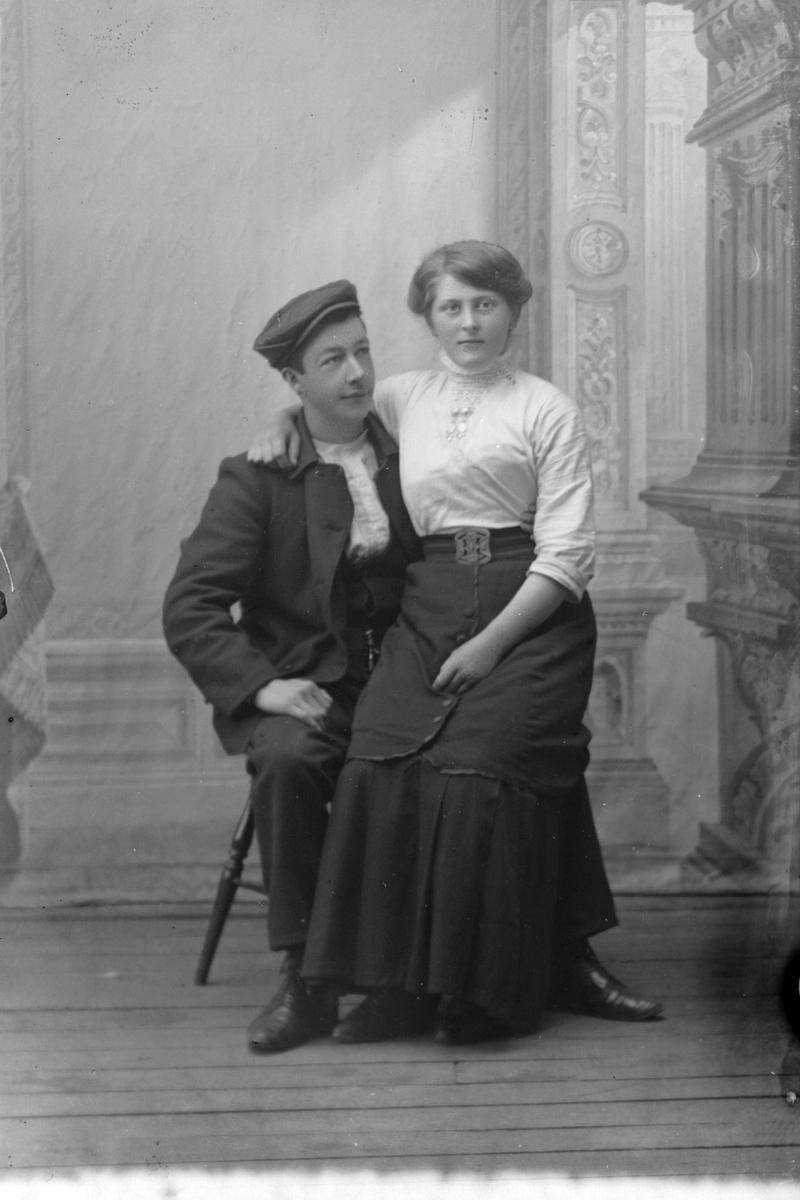 Studioportrett av en kvinne som sitter på en manns fang.