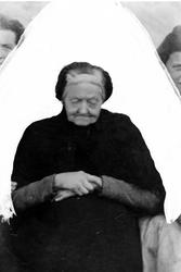 Studioportrett av en eldre kvinne som sitter.