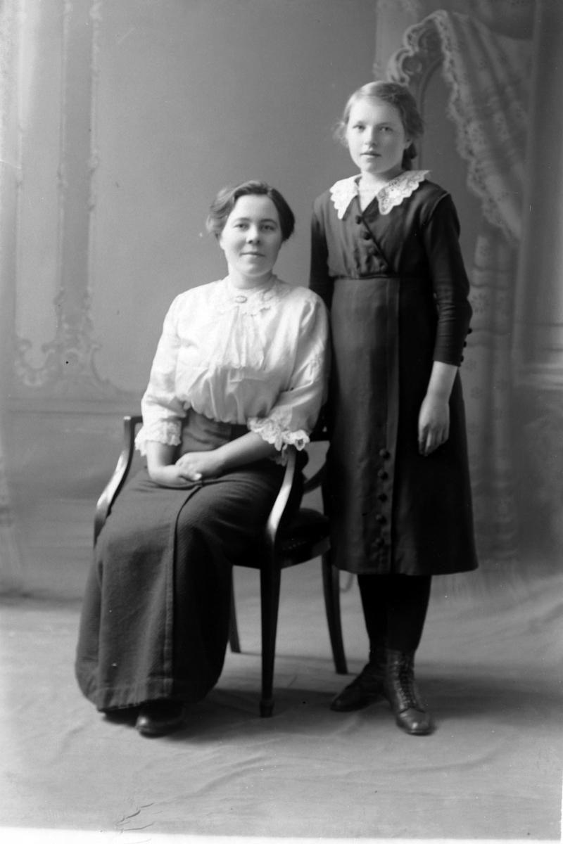 Studioportrett av en jente stående ved siden av en sittende kvinne.