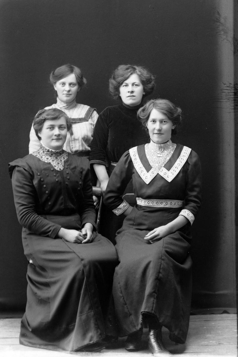 Studioportrett av fire kvinner i helfigur.