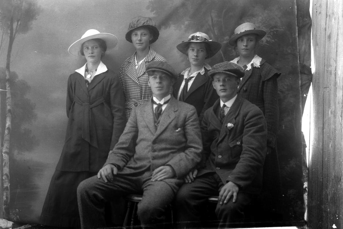 Studioportrett av to menn som sitter foran fire kvinner.