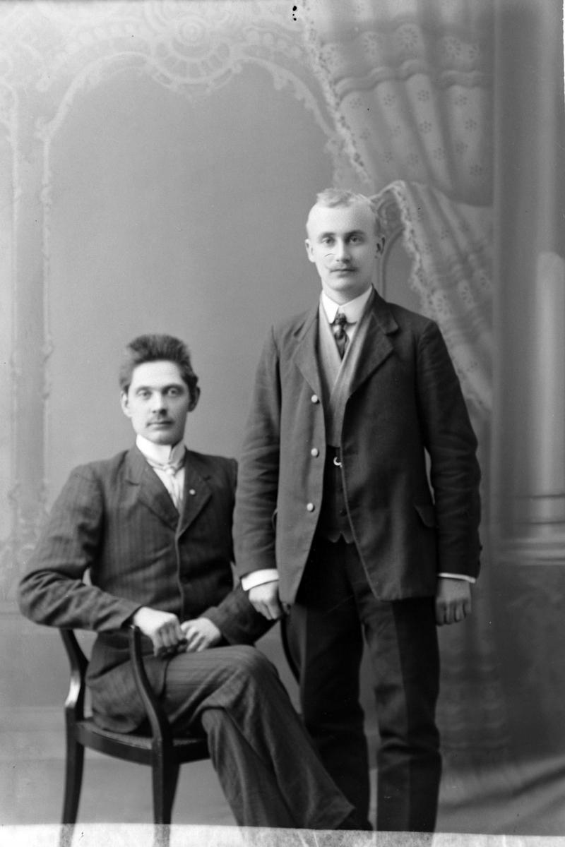 Studioportrett av én mann som sitter og én som står.