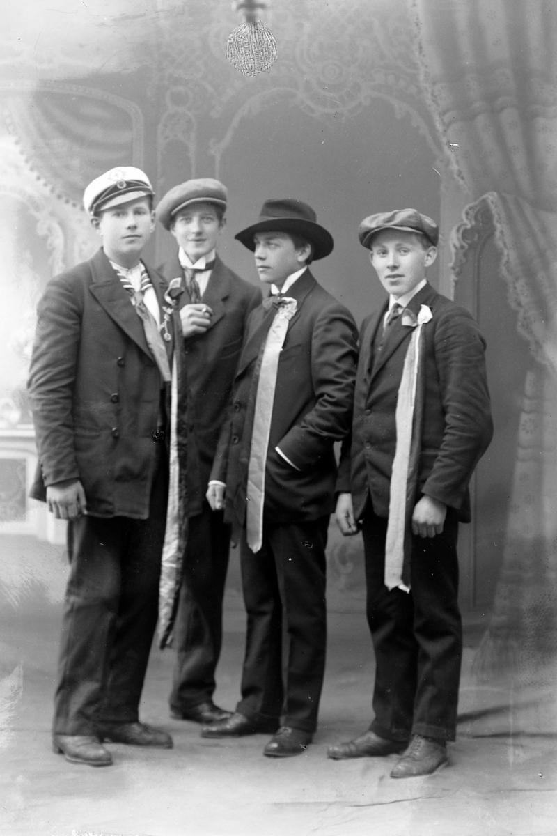Studioportrett av fire unge menn med sløyfer på brystet.