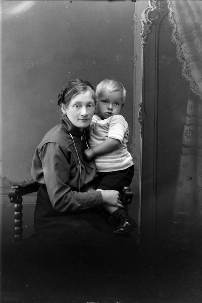 Studioportrett av en kvinne med et barn.