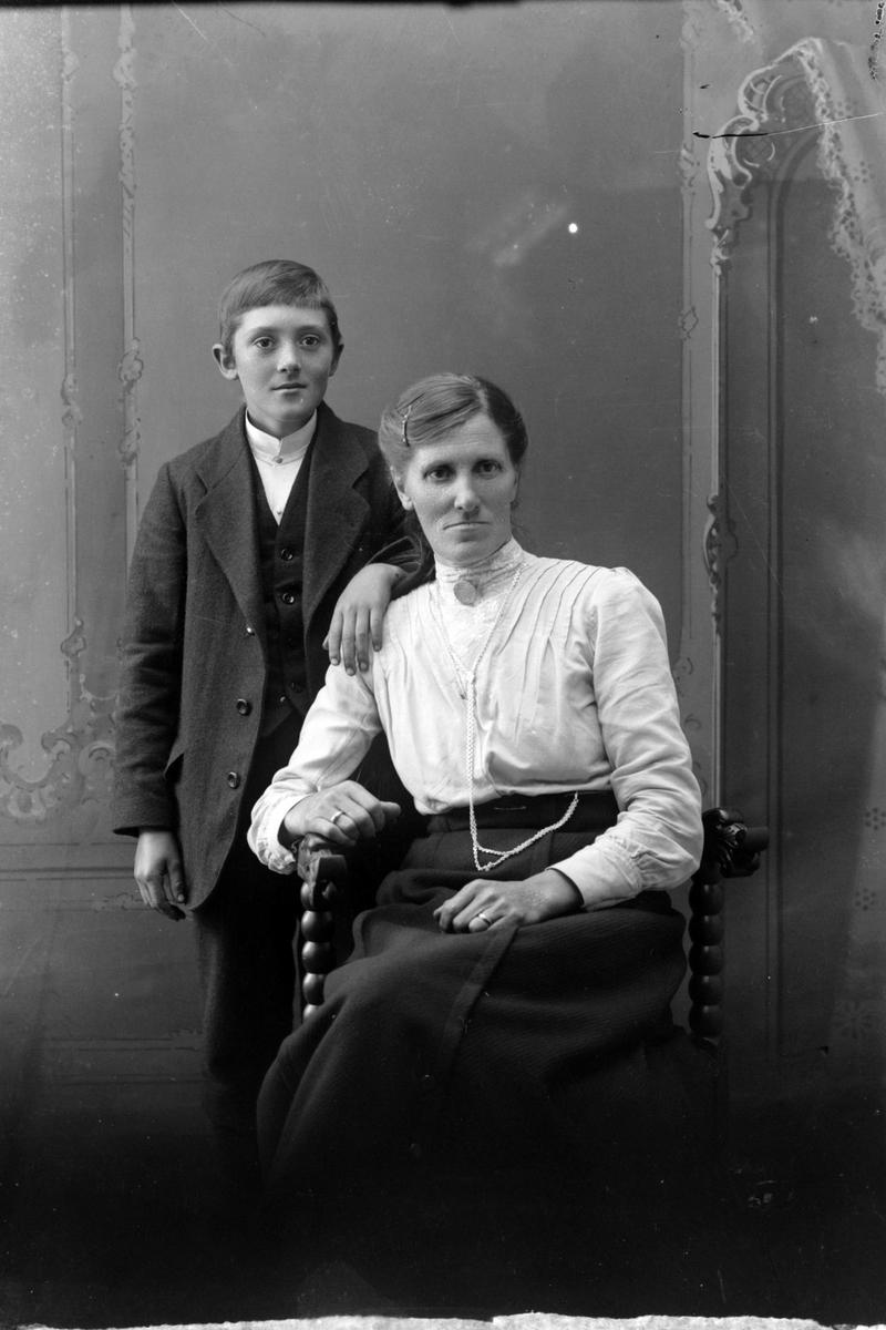 Studioportrett av en kvinne sittende foran en gutt.