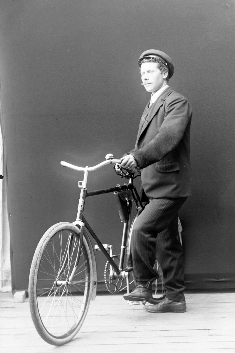 Studioportrett av en mann med en sykkel.