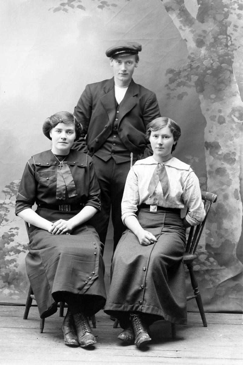Studioportrett av to kvinner sittende foran en mann som står.