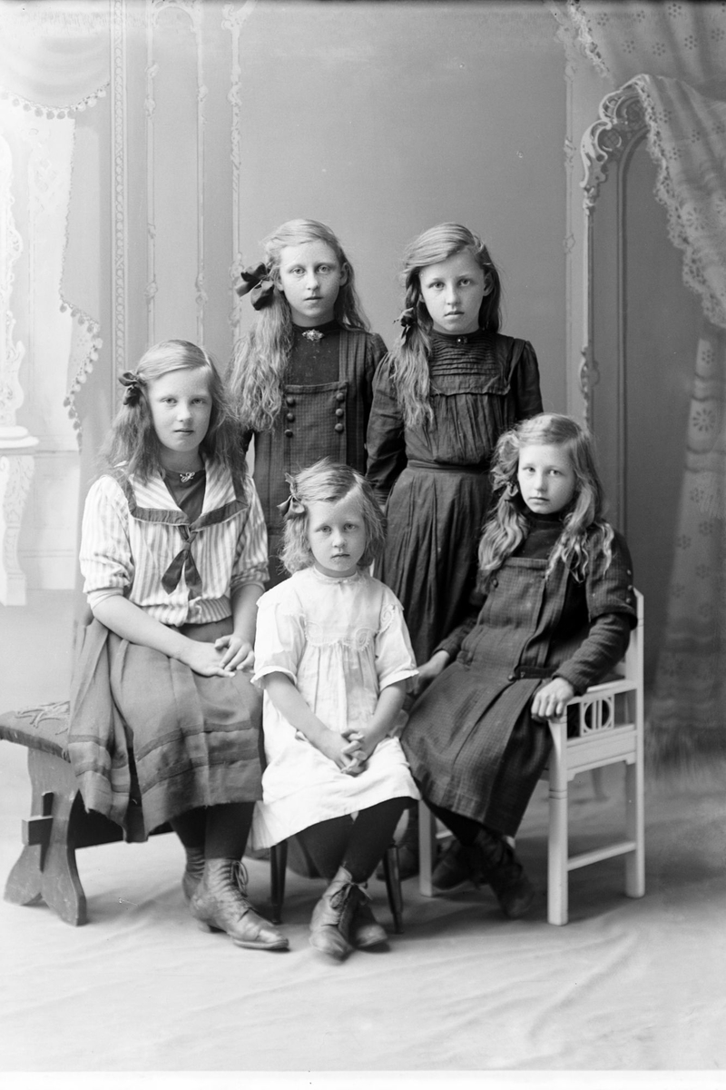 Studioportrett av fem jenter i helfigur.