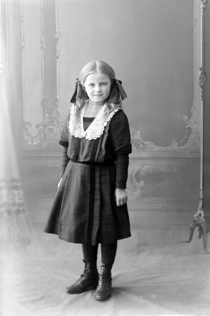 Studioportrett av en ung pike med sløyfer i håret.