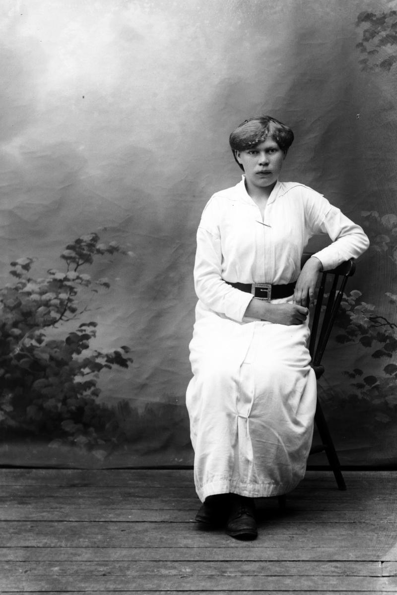 Studioportrett av en sittende kvinne i en lys kjole.