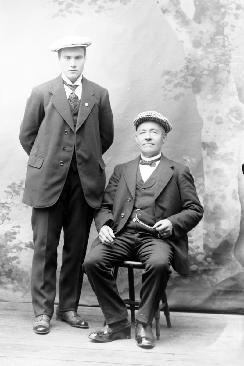 Studioportrett av to menn med luer på hodet.