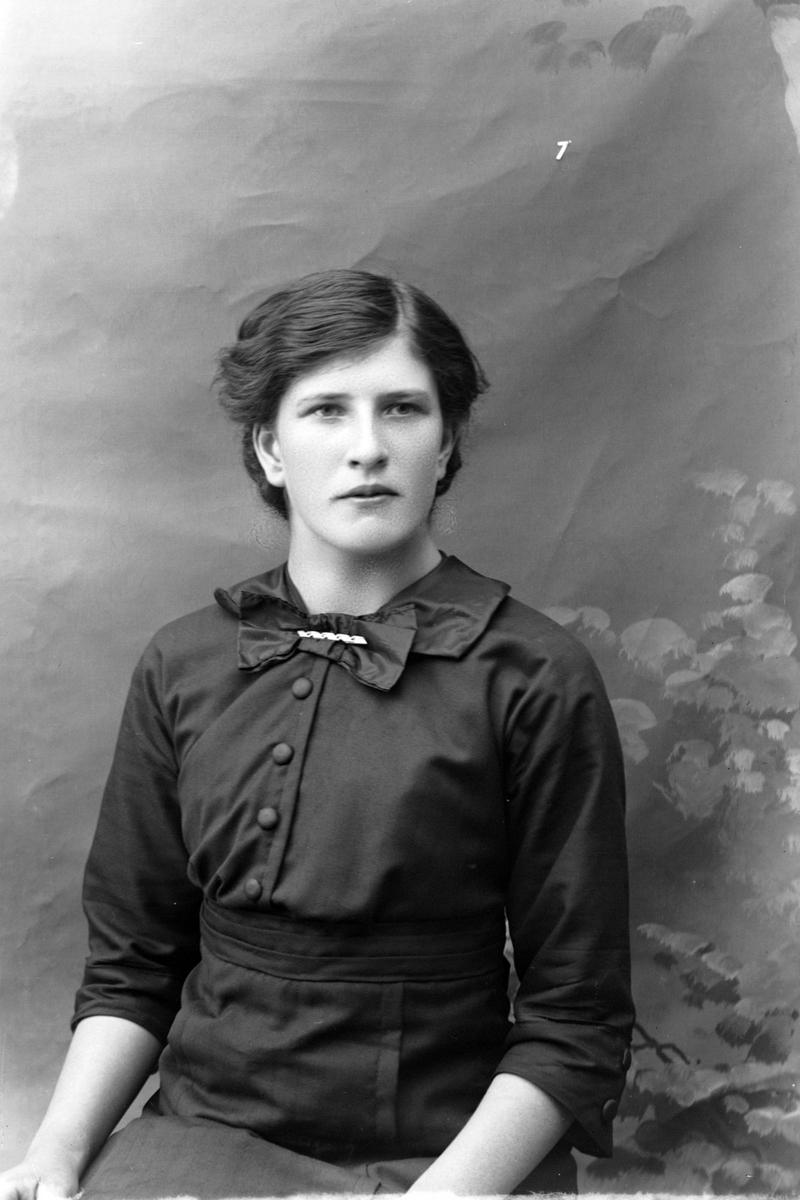 Studioportrett av en kvinne i en mørk kjole.