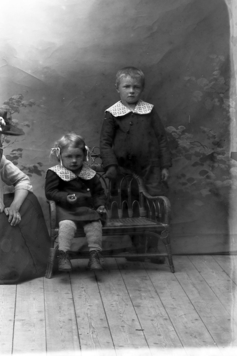 Studioportrett av to barn i helfigur, med en kvinne stående til venstre.