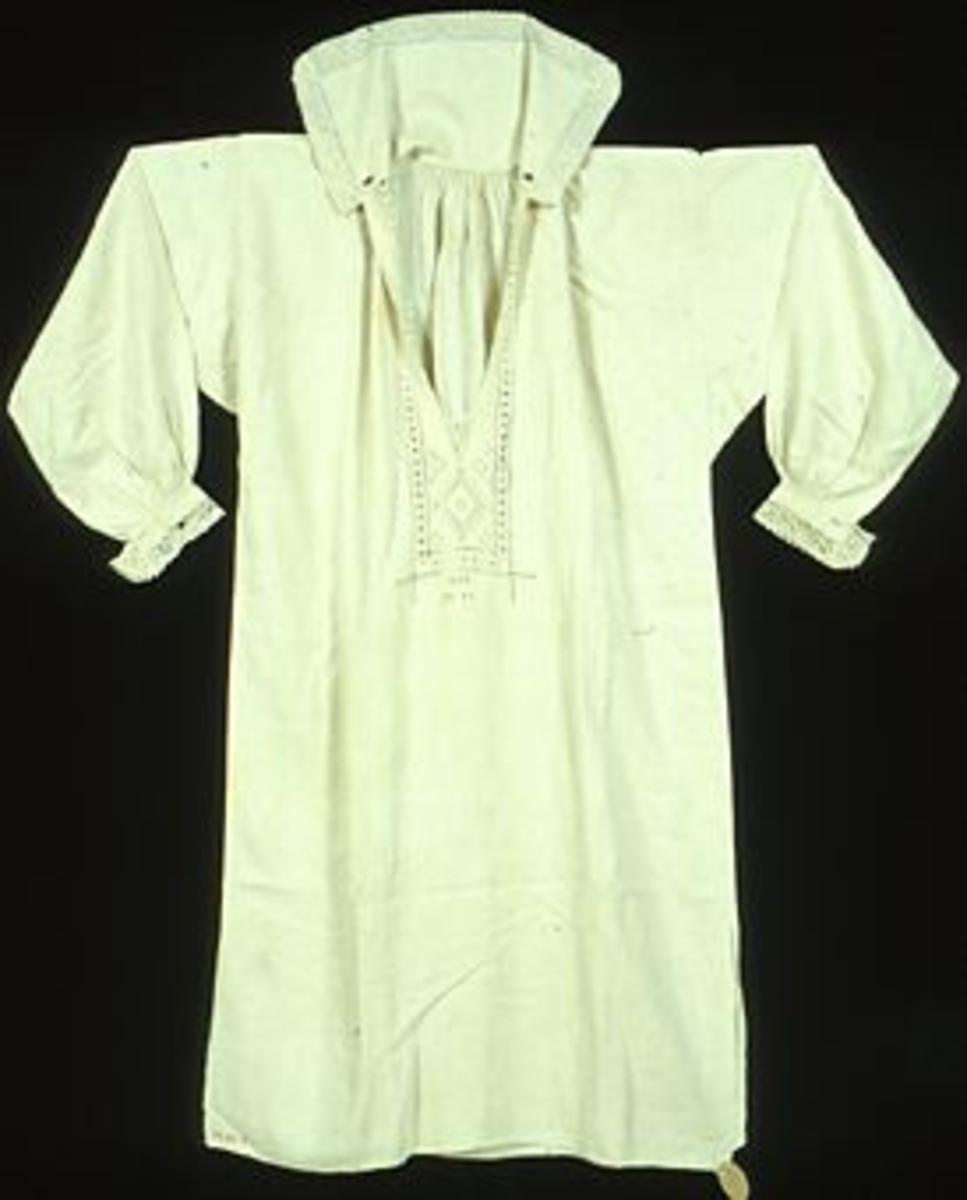 """Skjorta i linne med broderier och knypplad spets på krage, ärmlinningar och vid halssprundet. Skjortan är handsydd i halvblekt tuskaftad linneväv; ca 23 trådar/cm. Fram- och bakstycke är sytt på hel bredd; stadkanter invändigt i sidsömmarna. Ärmarna är ihopsydda med 4 mm breda fällsömmar. Bredd: 720 mm. Kragens höjd: 170 mm + 40 mm bred knypplad spets längs kanten. Kragen har en 65 mm bred broderad bård i udskårssöm och en smalare bård längs halva kortsidan i rätlinjig plattsöm. Kragen som ska stå rakt upp är fodrad med linneväv. Sprund mitt fram på bröstet, ca 340 mm långt, med sprundförstärkning av knypplad spets. Broderier runt sprundet mitt fram i tränsad hålsöm, udskårssöm och rätlinjig plattsöm. Under vitbroderiet på bröstet är skjortan märkt """"ALS 1740"""" i korssöm med rött bomullsgarn. Ärmspjäll: 110 x 110 mm.Halsspjäll: 130 x 220 mm, rynkat mot halsen. Ärmlängd: 570 mm. Ärmvidd: 560 mm. Ärmvidden regleras mot ärmlinningen med stripade rynkor. Ärmlinning: 220 x 27 mm + 30 mm bred knypplad Petterssonspets. Ärmlinningen är dekorerad med tränsad hålsöm. Ett 22 mm långt knapphål i var ände på ärmlinningarna. Ärmsprund: 110 mm + ärmlinning. Sidosömssprund nedtill: 310 mm långt. Längst ned i framstyckets ena hörn är skjortan märkt: """"N 20 B"""" med korsstygn i rött bomullsgarn. På samma ställe fast på avigsidan är ett tygband med invävd text fastsytt: """"SVENSK SLÖJD Malmöhus hemslöjd MALMÖ"""". I det andra hörnet hänger en fastnästad oval pappersetikett med blyertstexten: """"Nr 3""""."""