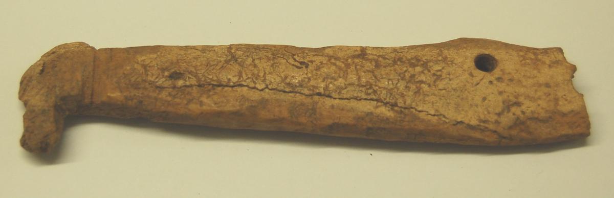 Gjenstanden har eit utskåret dyrehode i enden. I andre enden er det merke etter eit brudd. Der er i bruddkanten merke etter eit hull, og ca. 2 cm. inn fra kanten er der boret et hull.