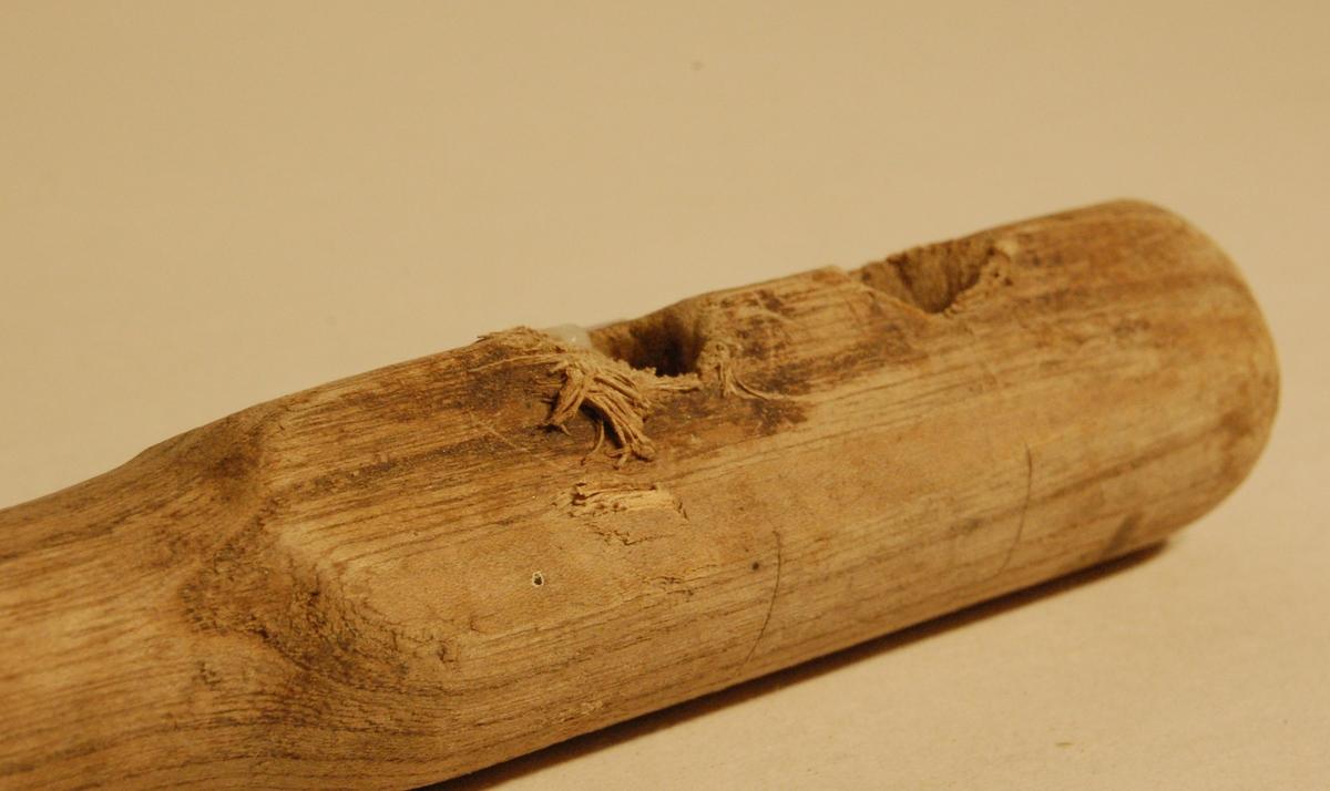 Knebelen er eit 19,5 cm. langt trestykke, med ein største diameter på 4 cm. I treknebelen er det boret to 10 mm. hull, med avstand senter - senter hull på ca. 3,5 cm.