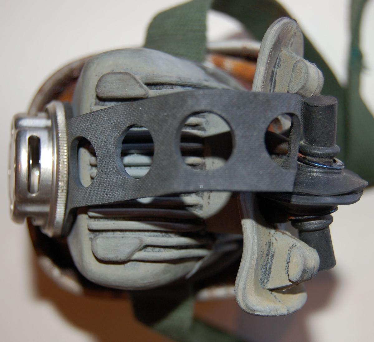 Rektangulært formet filter festet til et munnstykke til å putte i munnen, med tilhørende reimer til å holde filteret på plass
