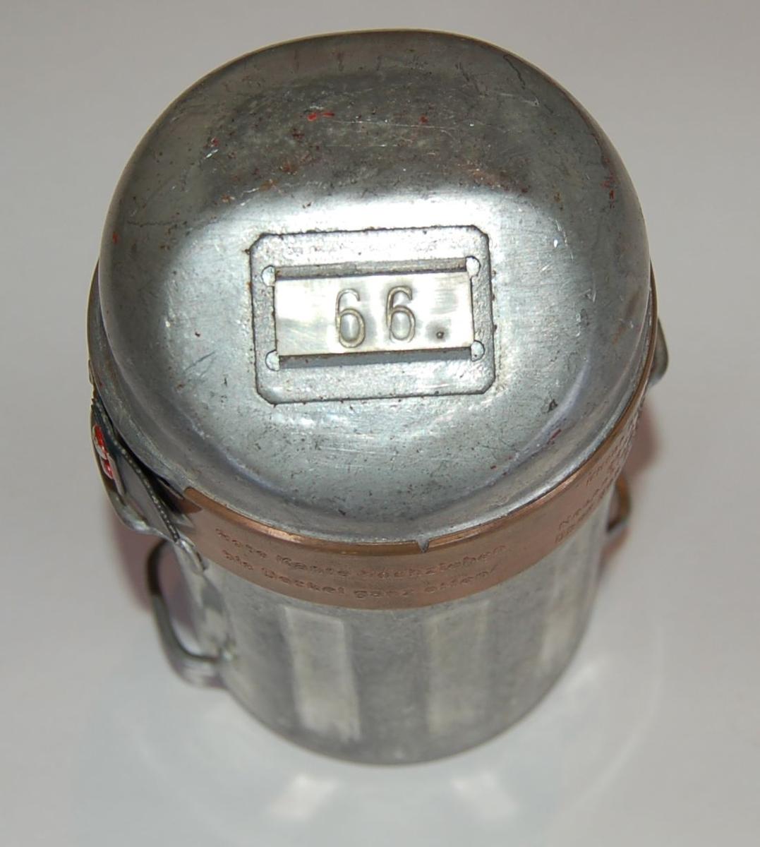 Sylindrisk metallboks inneholdende maske til bruk for å redde seg ut av gruva i tilfelle gass. Lokk med feste for nummerskilt, beltefester på sidene. Lokket er festet med et strammeband av kobber.