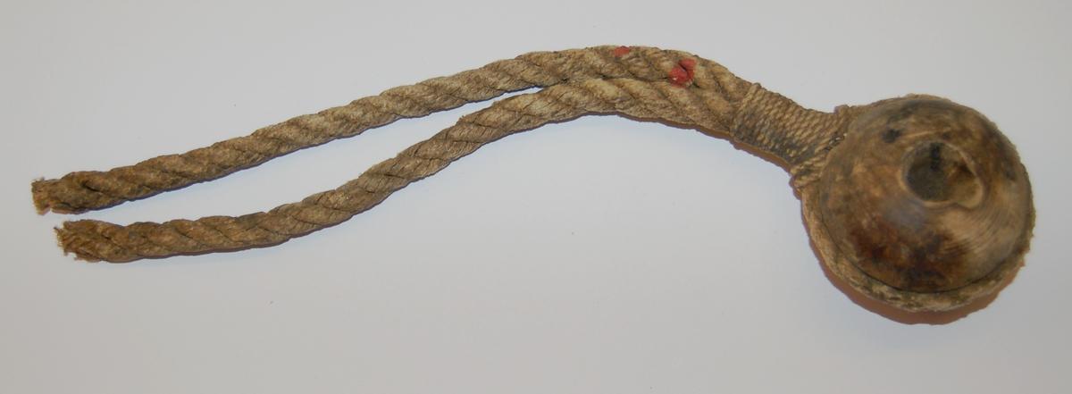 Kausen av hardtre er rund elipseformet, med eit hull i midten. Rundt kausen er det utfreset eit spor til tauet som skal festes til kausen.