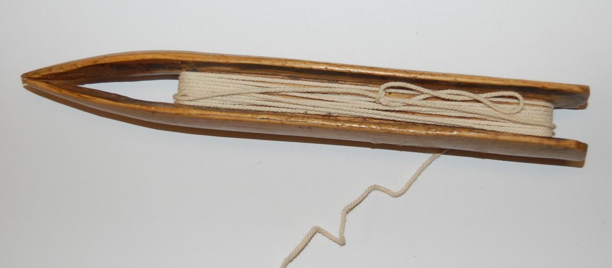 Nålen har en rektangulær form. I nålen er det utfreset et spor som tråden skal spoles opp på, og munnen på nålen er nebbformet med splittet ende.                                                                          På nålen er det en rest av bøtingstråd.