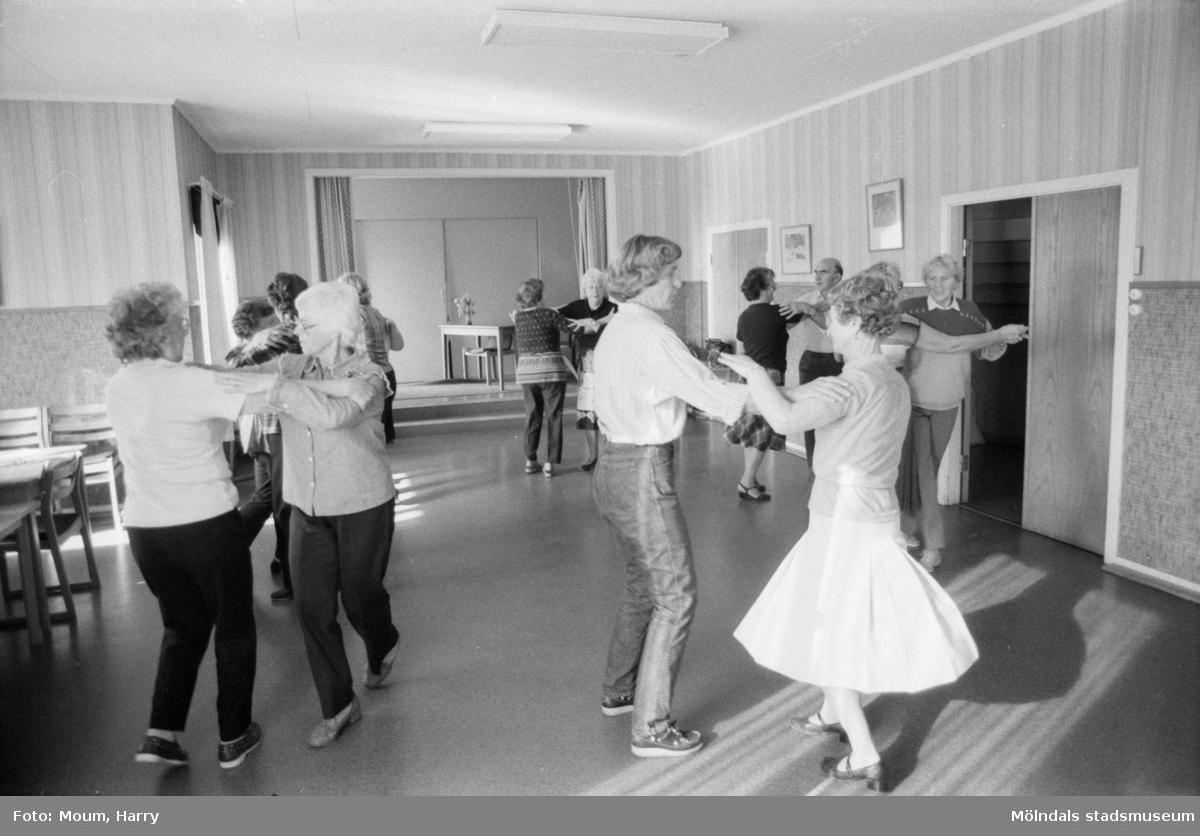 Mölndals-korpen anordnar aktiviteter för äldre i Mölndal, år 1984. Gammeldans. Kortet är taget i Kållereds kommunalhus, rivet i  början av 1990-talet. Adress: Streteredsv. 3. Kvinnan i mitten med jeans är ledaren Karin Gustafsson.  För mer information om bilden se under tilläggsinformation.